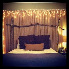 Canopy lit up with Christmas lights over bed: love this