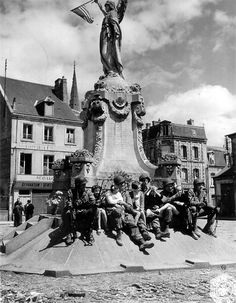Taking a moment of well deserved rest, troopers of the 101st sit before the Great War memorial with some French children they, and other Allied forces, recently liberated from German occupation.