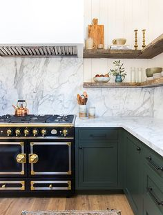 Dark blue-green cabinets lightened by white-grey marble countertops and well-traveled accessories look stunning in this kitchen.