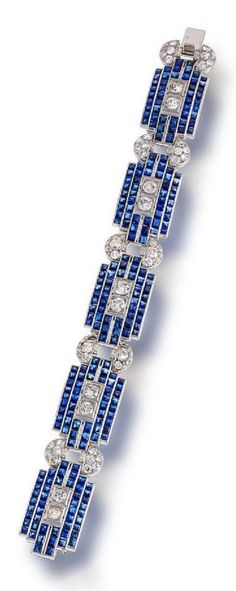 An Art Deco sapphire and diamond bracelet, circa 1935. Composed of geometric links set with calibré-cut sapphires, joined by old European and old mine-cut diamond half-moon shaped links, mounted in platinum.