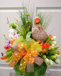 "This Easter basket arrangement is filled with an abundance of grasses, tulips, wax flowers, a large painted egg and a sweet sisal duck. The handle is tied with a multi-layered ribbon. Measures 19""H X"