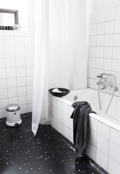 Clean and minimal bathroom with white tiles and dark terrazzo flooring.