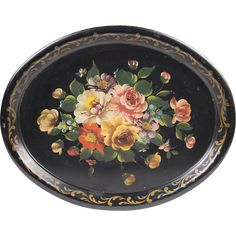 Presented for sale is a lovely early 20th century Tole tray with a lacquered black background hand painted with florals.  The tray is embellished with