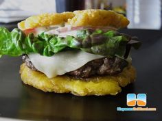Toston Burger / Pincho Factory / Nedal Ahmad - Heat 1 ounce canola oil to 320 degrees.  While the oil is heating up, peel the green plantains and smash or cut them into 2 inch buns.  Fry the slices in the hot oil for 10 minutes