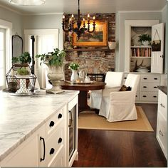 White kitchen, marble counter, black hardware; stone fireplace; slipcovered chairs