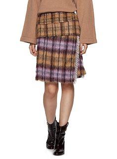 Cette mini jupe au jeu de carreaux beiges et lilas ajoutera une note sophistiquée à votre garde-robe automnale. Sa forme croisée en asymétrie et sa bordure frangée créent un look féminin des plus élégants.    Luxueux mélange de laine et d'alpaga au fini ultra doux   Fine doublure satinée   Fermoir zip dissimulé à l'arrière   Faite au Portugal    Le mannequin porte la taille 36