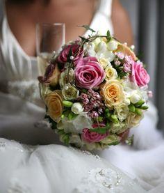 Bunter Hochzeitsstrauß in Kugel-Form mit verschiedenen Rosen und weißen Fresien. Verziert mit weißen Perlen aufgereiht auf feinem Draht.
