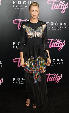 Charlize Theron wears aDior black silk butterfly-printed dress, chain-strap bag and black sandals at the premiere ofTully in L.A.