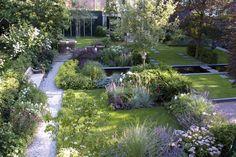Er gebeurt veel in deze tuin. Mooi gedaan. Opnieuw combi van strakke belijning en weelderige planten