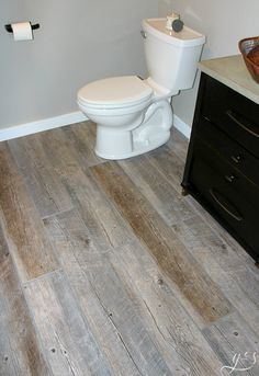 DIY How to Lay Floor Tile Planks | Our master suite bathroom floor is rustic and fun with the light tile that looks like wood and dark gray grout. These porcelain tile ideas and farmhouse designs are simple and beautiful. This tutorial to install your own large plank wood-look tiles on a budget will make you feel like a professional! I love the contrast of the grey-brown planks, white trim, dark vanity, and copper vessel sink. #farmhouse #tile #decor