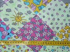 Katoenen stof met een print van ruiten/vierkanten met daarin hartjes, bloempjes, zonnetjes, kevertjes, wolkjes, eendjes enz... in verschillende kleuren