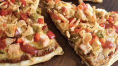 This delicious pizza is topped with refried beans, salsa, peppers, chicken, cheese and onion taco toppers.