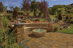 Curved cast stone retaining wall with contrasting ledges. Cambridge Pavers