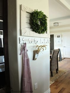 A lush boxwood wreath adds vibrant color to a muted wall