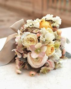 A lush clutch of roses, ranunculus, pieris, hellebores, and dusty miller.