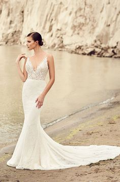 View Deep V-Neck Wedding Dress - Style #2100 from Mikaella Bridal. V-neckline lace bodice lined in Nude Tulle and Lace. Fit and flare Lace skirt.