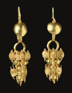 A PAIR OF ROMAN GOLD EARRINGS   CIRCA 3RD CENTURY A.D.   Each composed of a hoop of two plain and two beaded wires twisted together, tapering at one end and formed into a hook above a convex disk, the hoop supporting a pendant, the upper portion with two square sheets divided by a ribbed tube in the center, with four coiled volutes at the corners interspersed with beaded wire, the lower portion an inverted stack of hollow spheres with a ribbed tube extension terminating in a hollow sphere...
