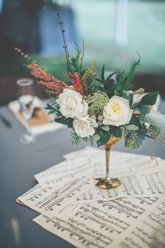 centerpieces with music sheets, photo by Papered Heart Photography ruffledblog.com/... #weddingideas #weddingcenterpieces #reception