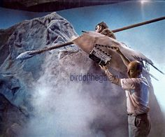 "In this clapper shot from the filming of ""The Galileo Seven"" we can see the anthropoid giant (played by the seven foot tall Buck Maffei)  that tormented Spock and the shuttle craft crew while they were stuck on Taurus II.   One of the creature's spears, its shield (which it later threw at Spock) blowing fog and the roof of the soundstage are also visible. This angle, with much more fog in the shot, appeared briefly in the episode absent the left part of the rocks and the roof of the…"