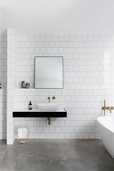 Bathroom with white square tile, concrete floor, modern freestanding tub