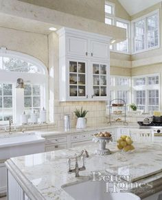 White kitchen with a hint of yellow tones on the walls and counter tops.