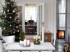 Scandinavian living room, with a silver fireplace, a Christmas tree and everything else is white. Natural Christmas, Christmas Mood, Noel Christmas, Scandinavian Christmas, Holiday Tree, Little Christmas, Xmas Tree, Christmas And New Year, Scandinavian Living