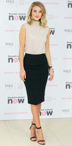 Rosie Huntington-Whiteley in an oatmeal sleeveless turtleneck knit tucked into a sharp black pencil skirt, with black ankle-strap sandals.