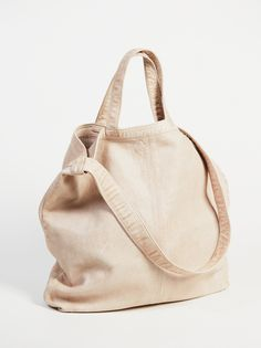 Simply Leather Tote   Real leather tote with a simple design and perfectly worn look. Features two short straps and a long shoulder strap for a customized carry. Suede inner with a zipped pocket.
