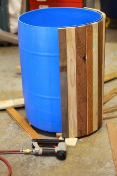 Reclaimed wood transforms a blue barrel (or ugly plastic pot) into a beautiful planter.