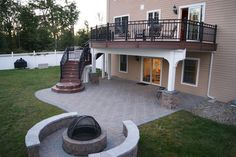 Second story, curved deck with stairs leading to paver patio and fire pit below.