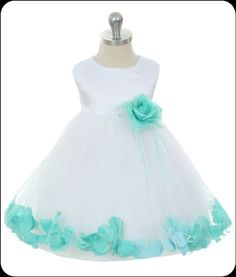 A beautiful bloom embellishes the waist of lovely white flower girls dress styled with a sleeveless bodice in your choice of shimmering satin or 100% silk; a double layer tulle overlay skirt is adorned with brilliant mint petals for an eye-catching finish.