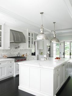 Love the combination of the deep wood floors, white cabinetry and marble and industrial light fixtures.