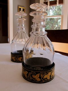 A pair of Regency era deep green and gilt decorated papier-mache wine coasters and decanters