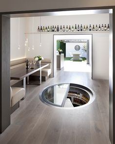 White Spiral Cellar with retractable round glass door - coolest. thing. ever.