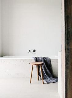 White marble tub built into wall and wood stool: