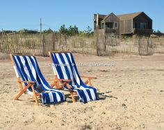 Two beach lounge chairs draped with blue striped beach towels sit empty on the beach on a sunny day at Fire Island. The chairs also have books sitting in them.