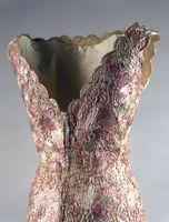 Designer: Oleg Cassini (American, b. France 1913-2006)  Date Made: 1961  Medium: Raffia lace  Evening dress in pink-and-white raffia lace with matching kerchief stole.  Fabric has scalloped edge at hem, neckline and arm holes.  Dress is fitted at waist and falls straight to the heel.  This dress was worn by Jacqueline Kennedy arriving at a dinner given by President and Madame Charles de Gaulle at the Elysée Palace, France on May 31, 1961.