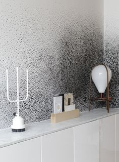 """In the hallway, Lafforest resorted to Ikea again for a basic console table, then added a luxurious slab of Carrara Marble to stylize the otherwise yawn-worthy casement piece. Droog candlesticks and Lafforest's own""""Olab"""" Lamp sit on top the marble, with an all too intriguing spotted wallcovering as the backdrop."""