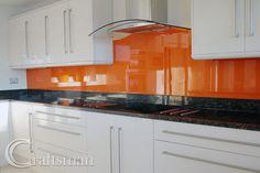 White units, black granite worktops, orange glass splashbacks