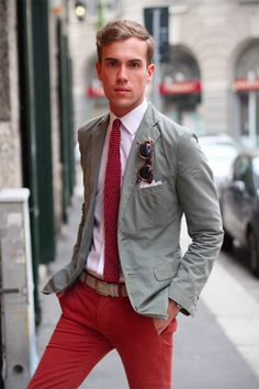 red chinos, beige belt, white shirt, grey jacket, red knit tie with white polka dots