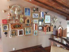 Parede rosa cheia de quadros e artesanato no restaurante Casa di Vina, localizado na casa onde vivia Vinícius de Moraes, na Bahia