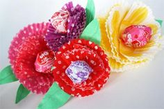 Paper baking cup flowers with lollipop centers.  Perfect for party favors or centerpieces. via skiptomylou.org