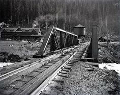 Great Northern Railway railroad bridge over the Tye River at Scenic.  The Scenic Hot Springs Hotel is at left and the depot is on the right.  May 25, 1913 photo