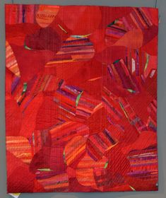 """""""Mighty Red"""" improvisational pieced quilt by Mary Jo Bowers, 2013 Fine Art of Fiber exhibit.  Strip pieced, cut and repositioned."""