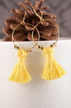 These trendy earrings were seen on the summer fashion magazines. The ear wires are gold filled with a lever-back for a secure fit. Each hoop has a mini cotton tassel and two metal beads on either side