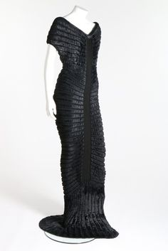 * 'Houpette' black chenille-knitted evening gown , Spring-Summer, 1994 Azzedine Alaïa . Sculpted figure-hugging dress with radiating concentric chenille bands, trained hem