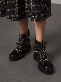 Italian-made buckled ankle boots in calf leather, elevated with polished gold-tone studs. The military-inspired design is offset by traditional brogue detailing and straps in contrasting textures.