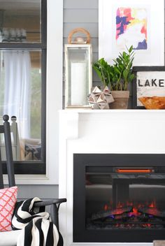 An electric fireplace provides extra warmth on a screened in porch when the weather is cool. See more of this three-season porch/living room styled by Jennifer Bridgman of The Chronicles of Home. || @chrniclesofhome