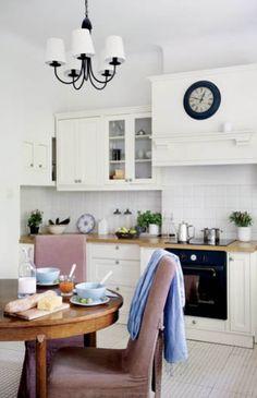 Stylowa kuchnia - W kuchni niemal niepodzielnie panuje biel. Tylko stół i krzesła wyłamują się z kolorystycznej dyscypliny, dodając wnętrzu przytulności, lecz nie odbierając lekkości. biel, pastelowe kolory, kuchnia, stylowa kuchnia, klasyczna kuchnia, jadalnia, szafki kuchenne, drewniany blat, okrągły stół