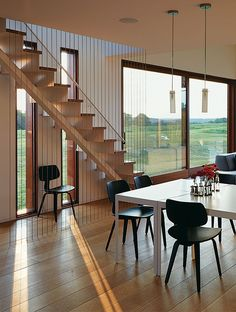 Stainless-steel cables along the stairs function as a second railing without blocking views through the adjacent windows. Tagged: Dining Room, Chair, Table, and Pendant Lighting. Photo 7 of 10 in A Prairie Escape Embraces the Landscape with a Green Roof.